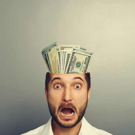 shocked young businessman with money in the head looking at camera and shouting over grey background photo