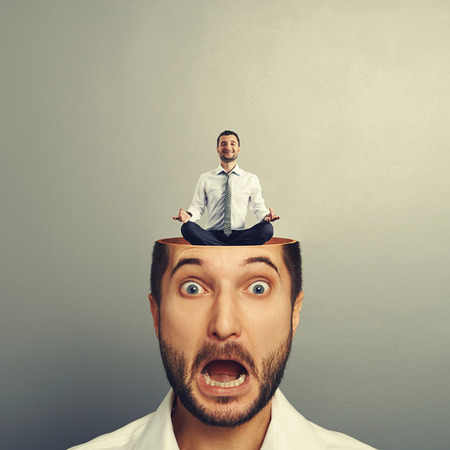 open minded: stressed businessman with open head. young calm businessman sitting in yoga asana and smiling in the mans head. photo over grey background