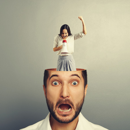 stressed businessman with open head. young angry businesswoman standing into the head, looking at the man and screaming with megaphone. photo over grey background Stock Photo