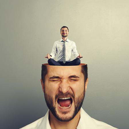 Portret van benadrukt jonge man met een open hoofd. kalme zakenman zitten in yoga asana en lachend in de man hoofd. foto over grijze achtergrond