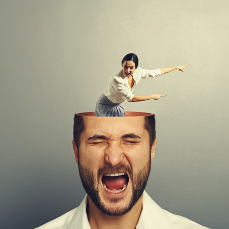 open brain: stressed man with open head. young screaming woman standing into the head, looking at the man and showing the direction. photo over grey background