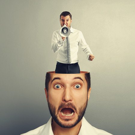 open minded: stressed young man with angry screaming man in his head over grey background