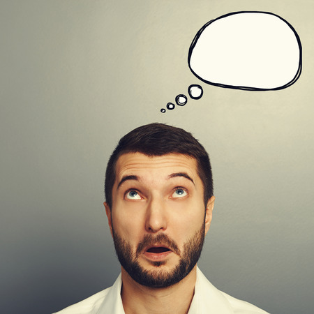 bewildered: amazed young man looking up at empty speech bubble. portrait over grey background Stock Photo