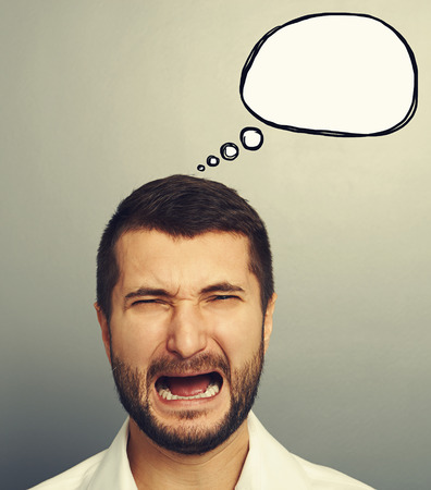wrath: portrait of emotional crying man with empty speech balloon over grey background
