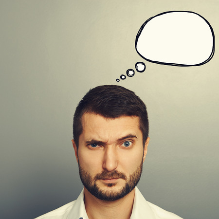 discredit: pensive man with empty speech bubble looking at camera over grey background