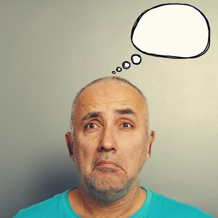 sorrowful: portrait of sorrowful senior man with white speech balloon over grey background