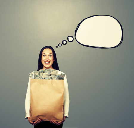 woman holding money: excited young woman holding paper bag with money. concept photo with drawing speech bubble over grey background