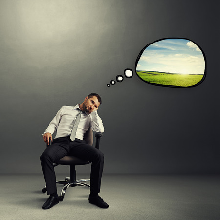 tiresome: bored businessman sitting on the chair with speech bubble and thinking about rest over grey background