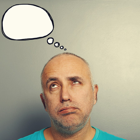tiresome: portrait of bored senior man looking up at speech bubble over grey background
