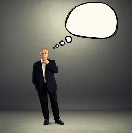 thinking serious businessman in formal wear with empty speech balloon over dark background photo
