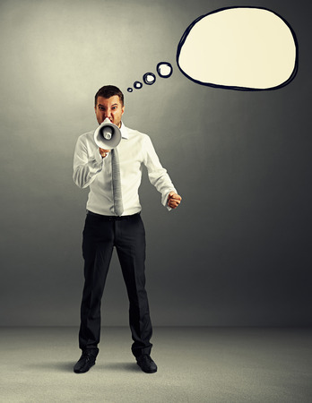 scold: angry businessman with speech balloon screaming at megaphone over grey background