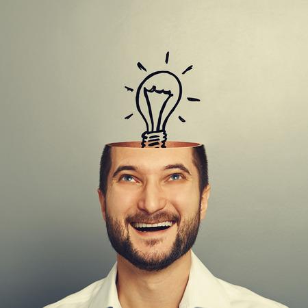 eccitato uomo d'affari smiley guardando lampadina nella testa. foto su grigio