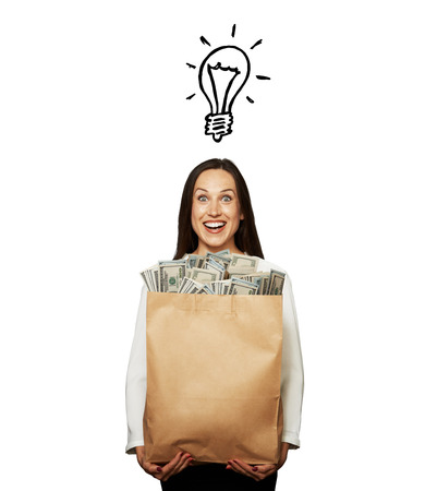 woman holding money: smiley young woman with drawing light bulb holding paper bag with money over white background