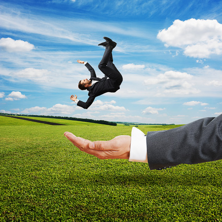 reliably: big palm catching small scared businessman over green field and blue sky Stock Photo
