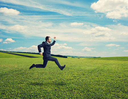 serious businessman in suit running fast at outdoor photo