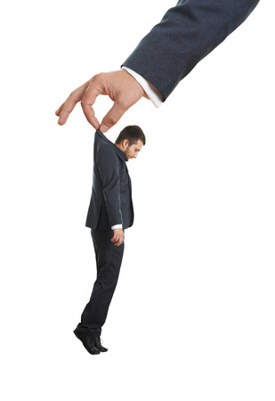 sorrowful: big hand holding small sorrowful businessman. isolated on white background