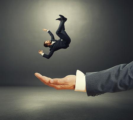 caida libre: palma grande captura de pequeño hombre de negocios sorprendida en una habitación oscura