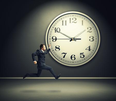 last minute: serious running businessman and big white clock in dark room Stock Photo