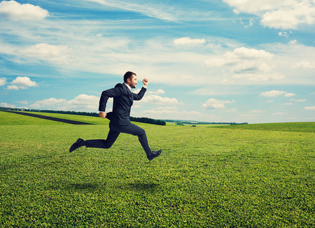 smiley businessman in suit running fast at outdoor photo