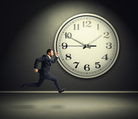 reloj: sonriente hombre de negocios corriendo y gran reloj blanco en el cuarto oscuro