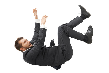 stressed screaming businessman in black suit falling down over white background Foto de archivo