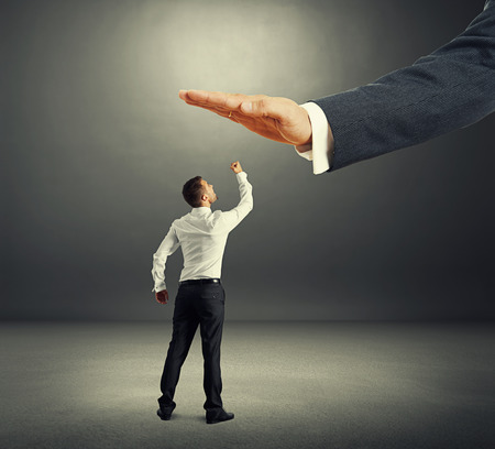 subordinate: concept photo of conflict between subordinate and boss. dissatisfied businessman looking up at big palm of his boss and showing in the dark room Stock Photo