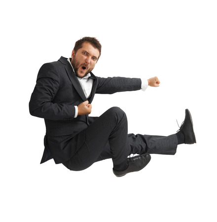 funny businessman in black suit kicking as karate. isolated on white background photo