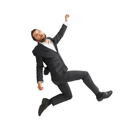 tumble down: sad businessman falling down over white background