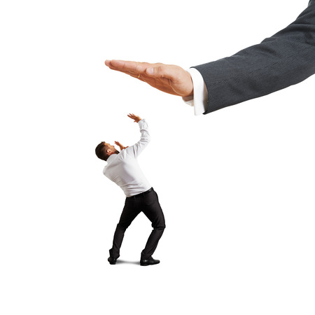 subordinate: concept photo of conflict between subordinate and boss. scared businessman looking up at big palm of his boss. isolated on white background
