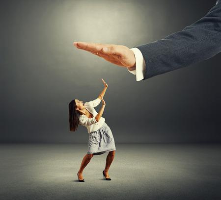 autoridad: Foto del concepto de conflicto entre subordinado y jefe. empresaria asustada mirando al gran palma de su jefe y gritando en el cuarto oscuro