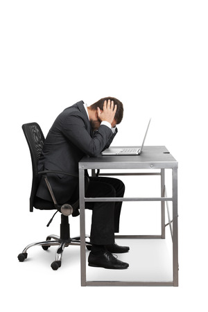 depressed businessman sitting at the table with laptop and covering his head. isolated on white background photo