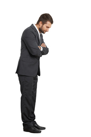 displeased businessman: displeased young businessman looking down. isolated on white background