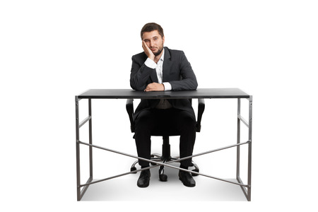 wearied: wearied businessman sitting at table and looking at camera. isolated on white background Stock Photo