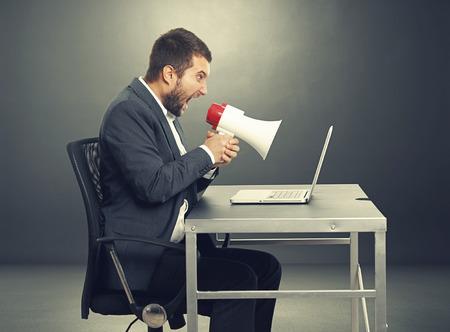 hombre megafono: hombre de negocios agresivo con meg�fono gritando y mirando port�til. la foto en el cuarto oscuro