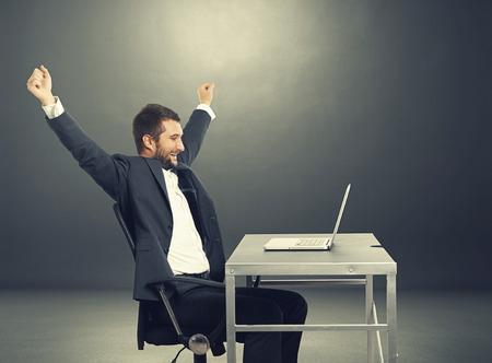 successful businessman raising hands up, looking at laptop and laughing. photo over dark background photo