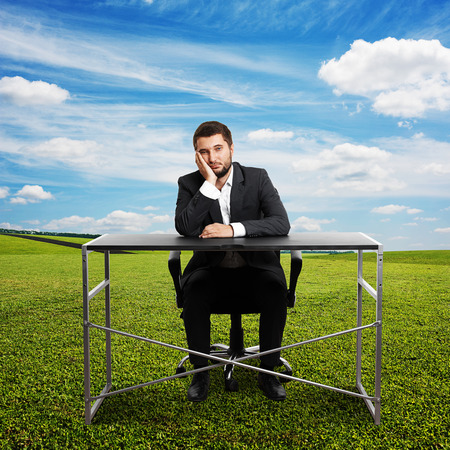 wearied: sad businessman sitting at the table and looking at camera. photo at outdoor