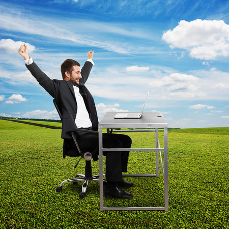 successful businessman raising hands up, looking at laptop and laughing. photo at outdoor photo