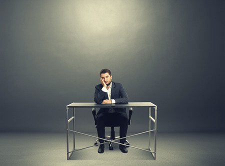 wearied: tired businessman sitting at table and looking at camera. photo in the dark room with empty copyspace