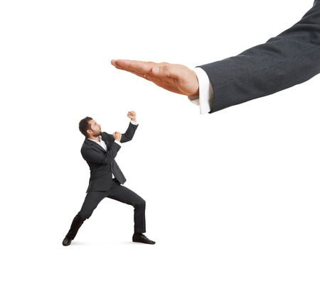 subordinate: concept photo of conflict between subordinate and boss. angry young businessman showing fist and looking up at big palm of his boss. isolated on white background Stock Photo