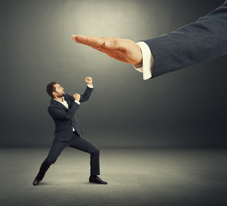 subordinate: concept photo of conflict between subordinate and boss. angry young businessman showing fist and looking up at big palm of his boss. photo in the dark studio Stock Photo