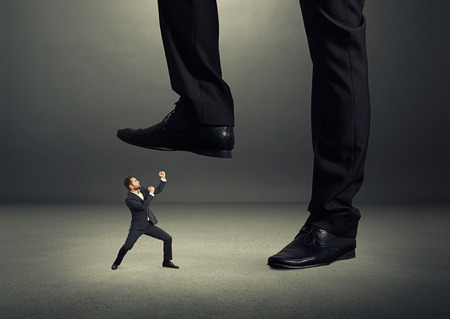 concept photo of conflict between subordinate and boss. angry young businessman showing fist and looking up at big boss. photo in the dark room photo