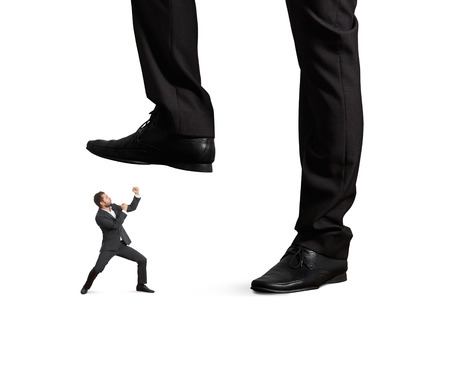 concept photo of conflict between subordinate and boss. angry young businessman punching and looking up at big palm of his boss. isolated on white background photo