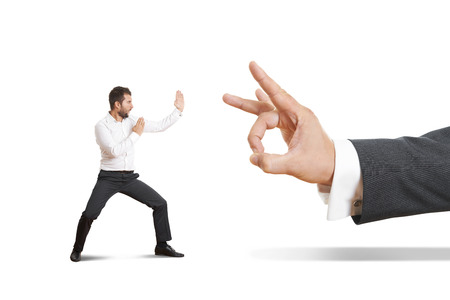 subordinate: concept photo of conflict between subordinate and boss. angry young businessman ready for fight with big flick of his boss. isolated on white background