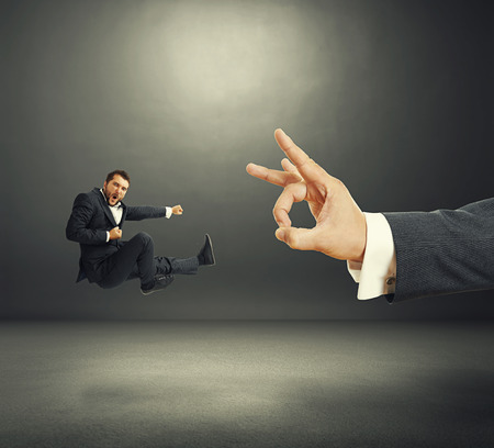 flicking: concept photo of conflict between subordinate and boss. emotional young businessman kicking and screaming, big hand flicking. photo in the dark room