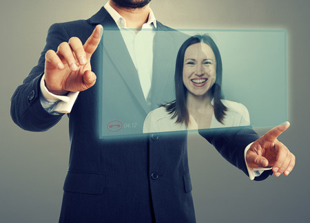 businessman and businesswoman communicating through video chat on virtual device. photo over dark background photo