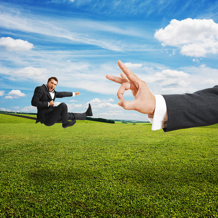 concept photo of conflict between subordinate and boss. angry young businessman kicking and flying at big flick of his boss. photo at outdoor photo