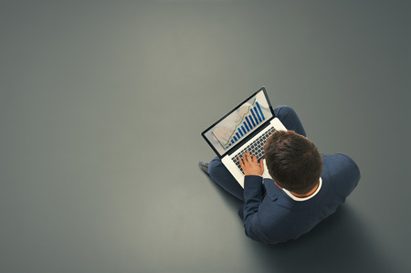 businessman sitting on the dark floor with laptop, typing and looking at growing diagram. view from above photo
