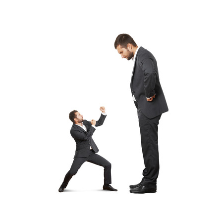 big and small: concept photo of conflict between subordinate and boss. scared small businessman waving his fists, displeased big man looking at him. isolated on white background