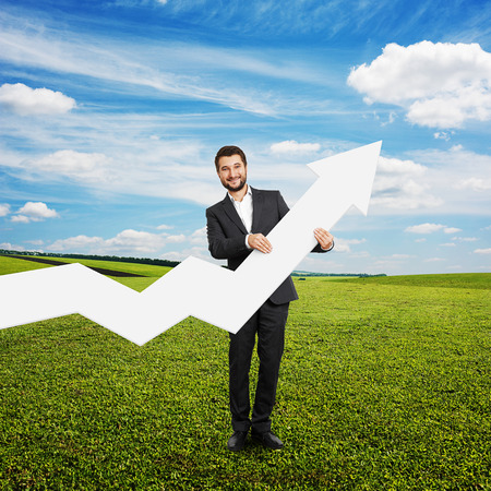successful businessman standing on the grass and holding white pointer photo