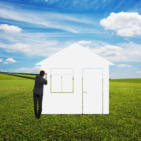 man hitting the nail on the wall drawing house. photo at outdoor photo